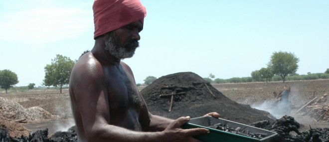 Man making biochar to capture carbon and promote organic agriculture