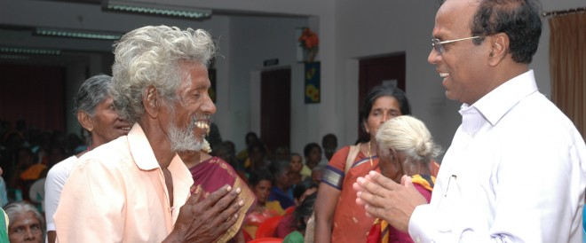 An elderly man thanking Cletus Babu for his support