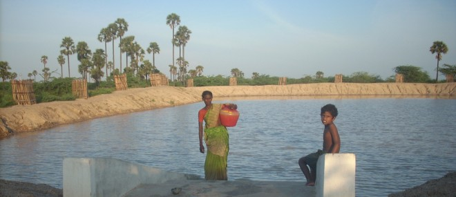 A woman and child taking water from an Ooranie in Southern India