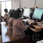 Children at a SCAD school learning how to use computers
