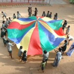 Children at Anbu Illam playing with a giant colour wheel